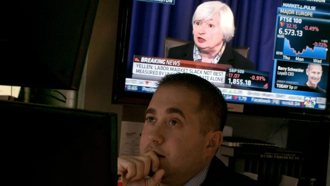 Federal Reserve Chair Janet Yellen's Washington, D.C. news conference is on a television screen behind specialist Gernaro Saporito as he works at his post on the floor of the New York Stock Exchange.