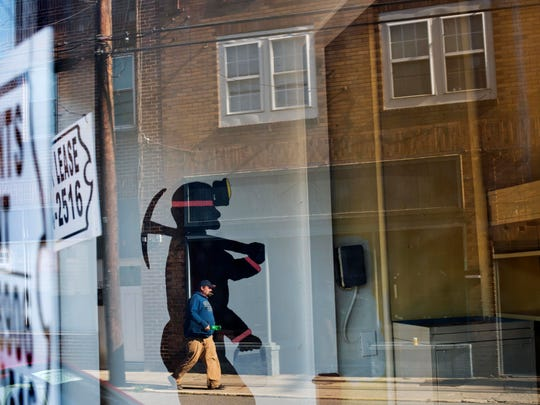A mural of a coal miner stands in an empty storefront
