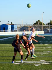 Carlsbad's Tessa Graham and Centennial's Jezalyn Aguirre (4) fight for possession in the first half Tuesday.