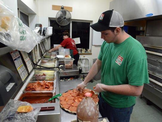 Tyi Coykendall makes a pizza Saturday night, May 12, 2018, at Cristy's Pizza in Amanda. Coykendall will graduate from Amanda-Clearcreek High School after making up nearly all of his school work in just two years.