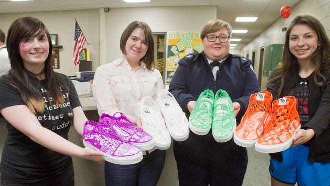 In this photo taken Friday, April 26, 2017, Howell High School students, from left, sophomore Audrey Paxton, seniors Veronica Schoemer and Sydney Rupp and junior Sydney Ormsbee were among a team of six in the school's advanced digital imaging class using a technique of sculpting with a 3-D pen over Van's-brand sneakers for a design contest hosted by the shoe manufacturer. Once the external structure was formed using the pens, it was lifted off and then the canvas was cut away and the pen-formed sculptural shoes were attached to the soles.
