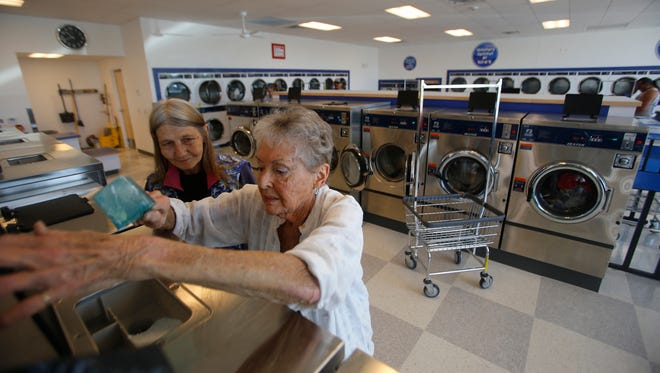 From left, Laundratopia attendant Lajuana Dufur helps customer Delora Charland on May 23 at a new Laundratopia in Aztec.