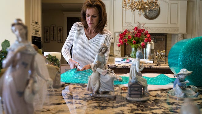 Karen Ippolito packs figurines in her 8,400-square-foot mansion near Shea Boulevard and 114th Street, which just sold for $2.5 million,.