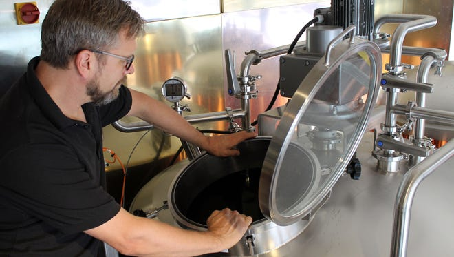 Water Street Brewery's brewmaster George Bluvas works with the new brew system.
