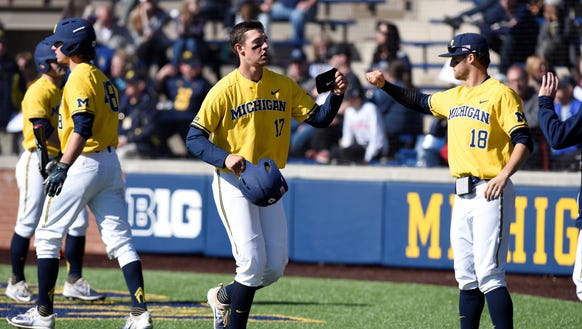 Michigan's Drew Lugbauer, left, and Jake Bivens bump