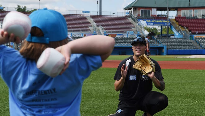"""Josie S., left, of East Fishkill, winds up a throw to the Renegades' Nicholas Padilla, right, at the throwing station during the """"Disability, Dream & Do"""" camp at Dutchess Stadium in Fishkill."""