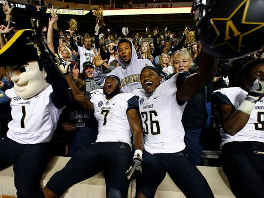 Vanderbilt mascot Mr. Commodore (1) celebrates with running back Ralph Webb (7) and wide receiver Trey Ellis (36) after an NCAA college football game against Tennessee, Saturday, Nov. 25, 2017, in Knoxville, Tenn. (AP Photo/Wade Payne)