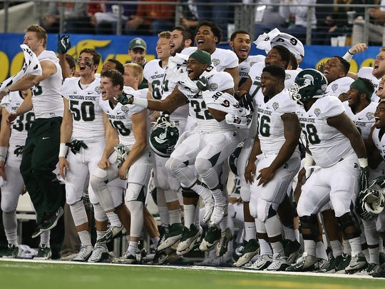 The Michigan State Spartans celebrate after a blocked