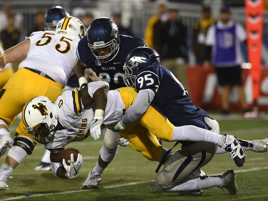 Nevada's Patrick Choudja tackles Wyoming's Brian Hill during a game in 2016.