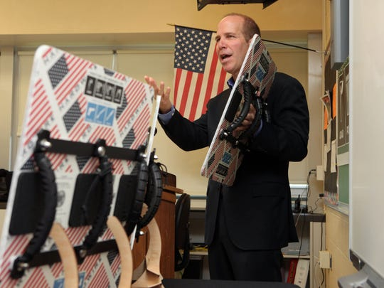 George Tunis, chairman and CEO of the civilian armor company Hardwire, demonstrates the use of the bulletproof whiteboard at a 2014 press conference announcing the pilot program that will supply the boards to students at Gunning Bedford Middle School.