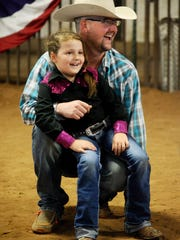 Michael Guthrie holds his daughter, Wailey, after she competed in the stick horse competition during the Western Heritage Classic.