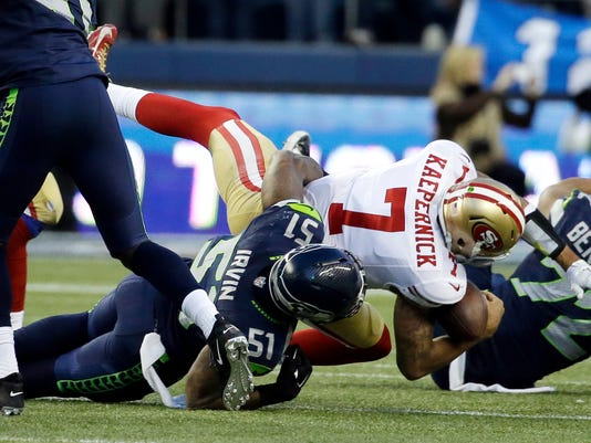 San Francisco 49ers quarterback Colin Kaepernick (7) is sacked by Seattle Seahawks outside linebacker Bruce Irvin in the second half of an NFL football game Sunday, Dec. 14, 2014, in Seattle. (AP Photo/Elaine Thompson)