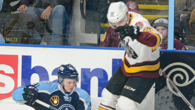 Admirals center Vladislav Kaminev tries to slap the puck out from between the skates of Chicago Wolves center Wade Megan after their collision knocked Kamanev to the ice.