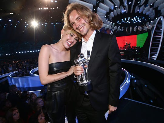 Singer Miley Cyrus (L) and My Friend's Place representative Jesse Helt, a Salem native, attend the 2014 MTV Video Music Awards at The Forum on August 24, 2014 in Inglewood, California.
