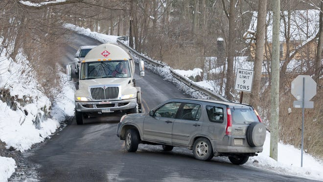 A small SUV swings in front of a propane tanker as it turns on to Stone Quarry Road from Spencer Road.