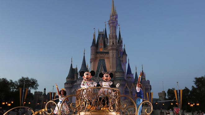 In this photo from Jan. 15, Mickey and Minnie Mouse perform during a parade as they pass by the Cinderella Castle at the Magic Kingdom theme park at Walt Disney World in Lake Buena Vista. The Disney and Universal parks are closing and will be closed through the end of March.