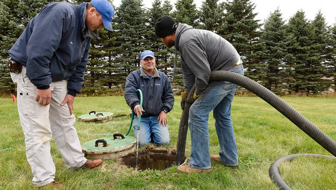 Ben Pflueger and Don Fischer of Watab Inc., talk with Max Posch of Tri-County Septic, as they prepare to inspect the tanks after they are pumped at a home for sale Thursday, Nov. 5 near Opole.