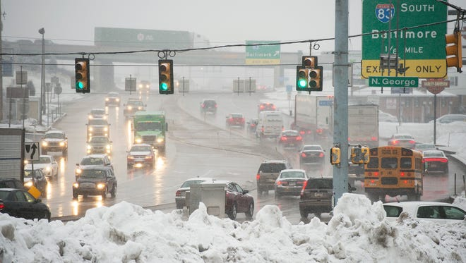 Traffic at the intersection of Route 30 and Interstate 83 in snow Tuesday runs smoothly behind old snow piles.