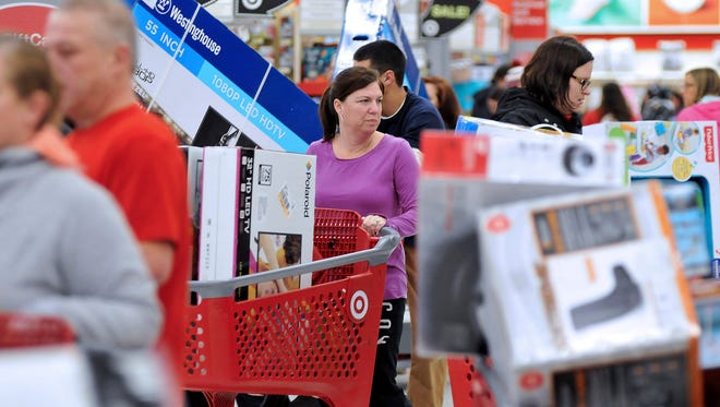 Shoppers maneuver through this Target store in Plainville, Mass., shortly after the store opened at 1 a.m. Friday, Nov. 25, 2016. Large screen televisions were among the popular items purchased.