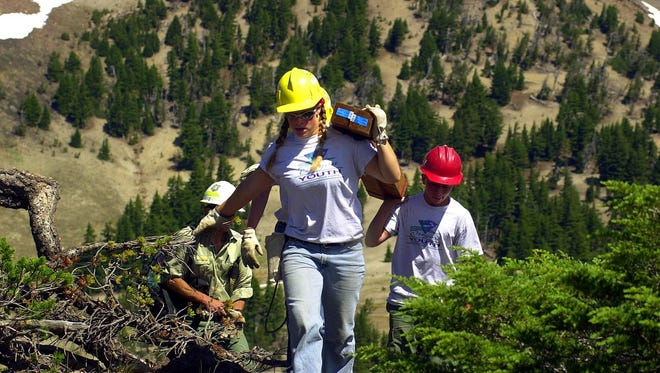 Members of a Bend-based Oregon Youth Conservation Corps help a group of scientist pack gear and supplies to a location south of the South Sister to establish a seismology station.