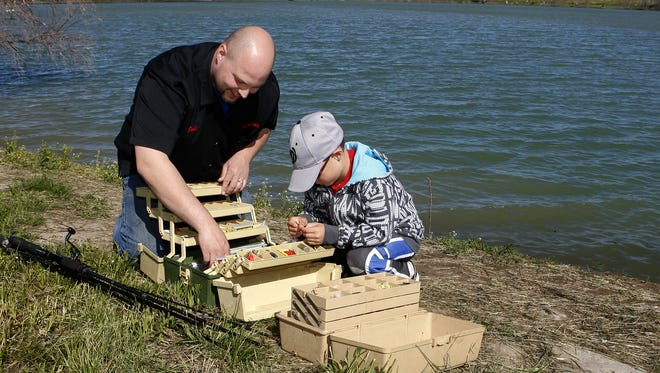 Josh Peterson and his son, Hunter, 9, go through their tackle as they get ready to fish during a previous Kids' Fishing Day at Wadsworth Pond.