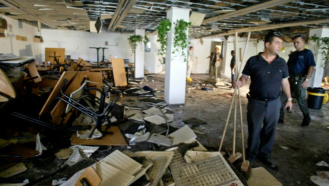 In this July 31, 2002, file photo, workers clean the inside of a cafeteria hours after a bomb exploded at Hebrew University in Jerusalem, killing nine, four of them Americans, and wounding more than 70.