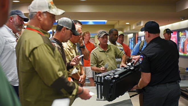 Al Courtney, of Jackson, Miss., gets his shotgun from Rick Tasso, with Sioux Merchant Patrol, Friday, Oct. 14, 2016, at the Sioux Falls Regional Airport ahead of Saturday's South Dakota Pheasant hunting opener. Courtney said this will be his second year hunting pheasants in South Dakota.