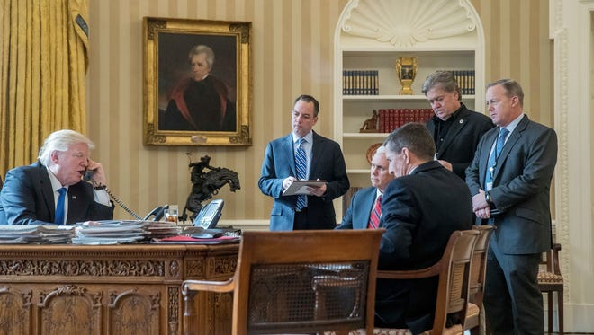 In this Jan. 28, 2017 file photo, President Donald Trump, accompanied by from second from left, Chief of Staff Reince Priebus, Vice President Mike Pence, National Security Adviser Michael Flynn, Senior Adviser Steve Bannon, and White House press secretary Sean Spicer, speaks on the phone with Russian President Vladimir Putin, in the Oval Office at the White House in Washington. President Donald Trump's chief strategist Steve Bannon is leaving his White House post.