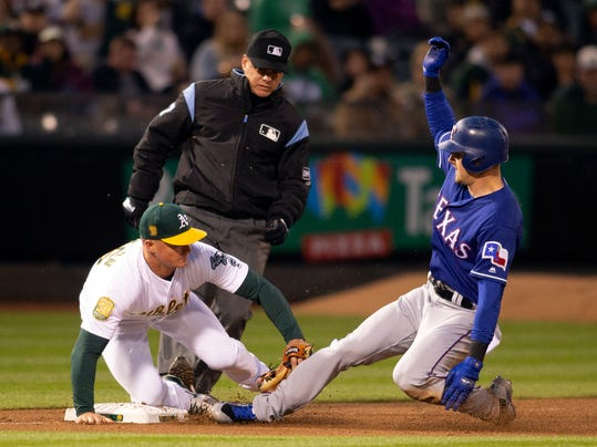 Oakland Athletics third baseman Matt Chapman (26) fields the relay in time to tag out Texas Rangers left fielder Ryan Rua attempting to steal third base during the second inning of a baseball game Tuesday, April 3, 2018, in Oakland, Calif. Umpire is D.J. Rayburn. (AP Photo/D. Ross Cameron)