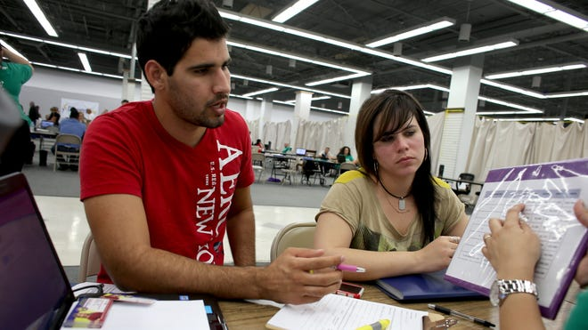 Jose Villanueva and Doraisy Avila look at a pricing plan with an agent from Sunshine Life and Health Advisors on March 31 in Miami.
