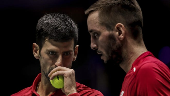 FILE - In this Nov. 22, 2019, file photo, Serbia's Novak Djokovic, left, and teammate Viktor Troicki play against Russia's Karen Khachanov and Andrey Rublev during the Davis Cup quarterfinal doubles match in Madrid, Spain. Another tennis player has tested positive for the coronavirus after taking part in an exhibition series organized by Novak Djokovic in Serbia and Croatia.Viktor Troicki said Tuesday, June 23, 2020, that he and his pregnant wife have both been diagnosed with the virus. The former top-20 player from Serbia played against Djokovic in Belgrade during the first part of the two-leg tour.