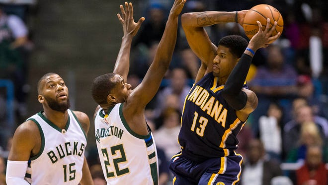 Indiana Pacers forward Paul George (13) passes the ball as Milwaukee Bucks guard Khris Middleton (22) defends during the first quarter at BMO Harris Bradley Center.