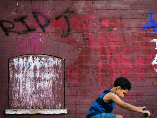 A young boy rides by RIP graffiti on the wall along