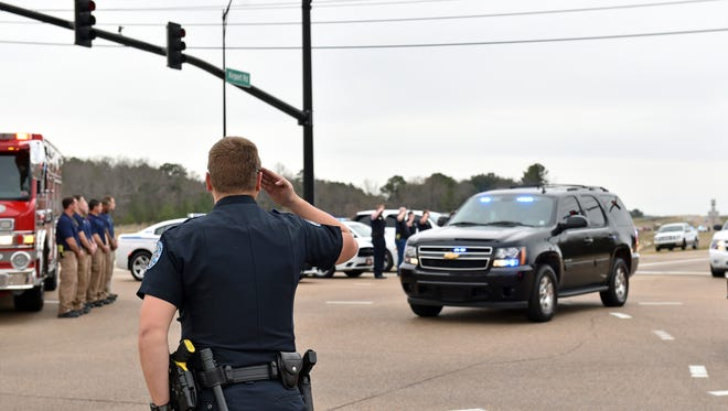 Police officers salute as a motorcade escorts the body of Mississippi Bureau of Narcotics agent Lee Tartt, 44, through Pearl to the Mississippi Crime Lab. Tartt was killed in the line of duty in a standoff situation in Tishomingo County early Saturday morning.