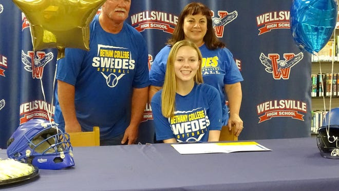 Wellsville High School senior Maggie Heath, sitting between parents Robert and Heather, signs to play softball with Bethany College.