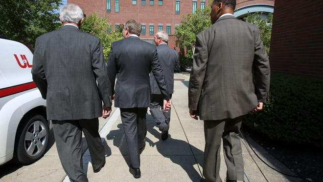 University of Louisville Board of Trustees Chair David Grissom, left, and interim president Greg Postel leave a press conference after announcing that athletic director Tom Jurich and men's basketball coach Rick Pitino have been placed on administrative leave from the school.  Sep. 27, 2017