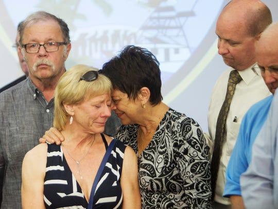 Jan Cornell, center, and Susan Gibson, left, react