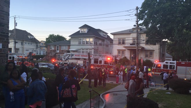 Firefighters and residents gather at the scene of the fatal Mount Vernon apartment fire on Saturday, June 3, 2017.
