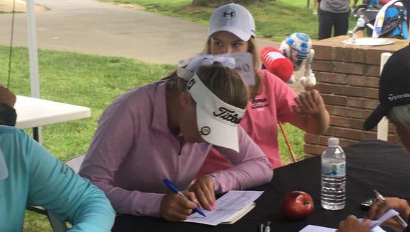 Lauren Peter signs the winning scorecard after the