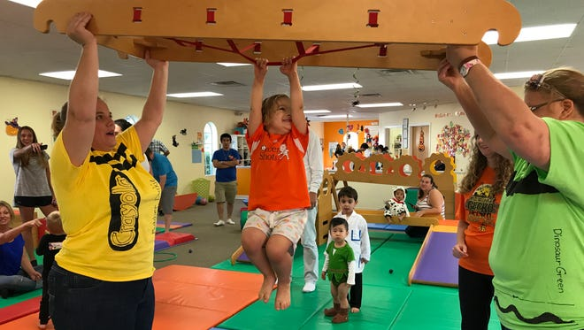 Isabella has fun hanging around as Miss Jill and Miss Denise of Gymboree in Melbourne hold her up during a Halloween party this past weekend.