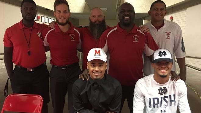 Fa'najae Gotay (seated, left) and Joe Wilkins Jr. pose with the North Fort Myers High football coaching staff, including head coach Earnest Graham (standing, second from right) on the first day of the early signing period, Dec. 20, 2017. Gotay signed with Maryland and Wilkins with Notre Dame.