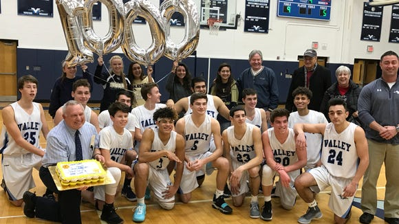 Joe Leicht, kneeling wearing tie, receives balloons and a cake after winning the 1000th game of his coaching career Saturday at Wayne Valley.