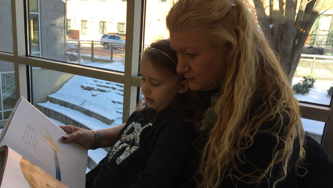 Pennie Tackett, right, reads a book with her granddaughter, Karma Jordan. Tackett is among Kentucky seniors who are pleased that Kinship Care, which provides funding to relatives taking care of children removed from their homes, may return. Jan. 18, 2018