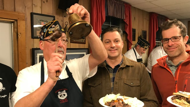 American Legion Post Abjutant Mark Corgiat (left) rings the bell for first-time raccoon eaters Rick Gray (middle) and Jason Hoffe.
