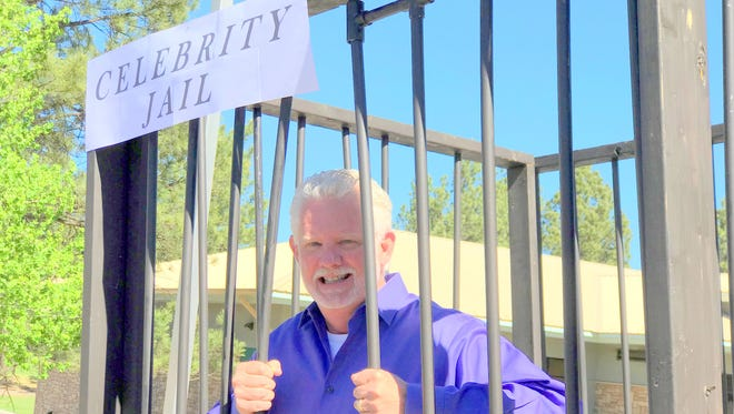 Ruidoso Mayor Lynn Crawford waits behind mock bars to be bailed out in a preview of part of the fundraising effort June 2 for the High Mountain Youth Project.