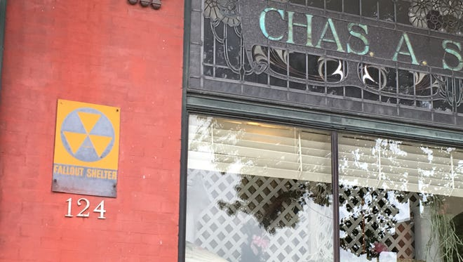 A weathered Civil Defense fallout shelter sign on the front of the older Chas. A. Schaefer Flower Shop at 124 W. Market St.