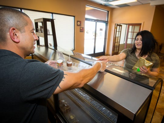 Co-owner of A Touch of Chocolate Abel Rivera, left, sells some chocolate marshmallows and gummy bears to customer Jackie Wilkinson, April 15, 2016.