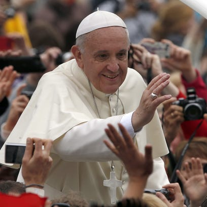 Pope Francis is driven through the crowd after presiding