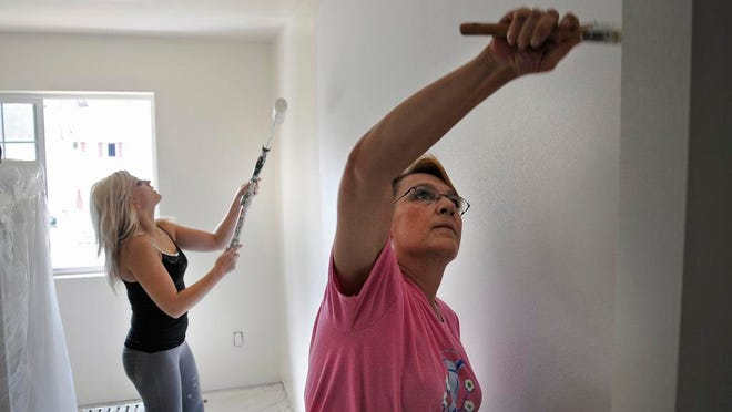 Volunteers Diane Shelander, right, and Jennifer Lesmeister paint the walls of a room in the Women Build Habitat for Humanity project house on Third Street North in St. Cloud Wednesday.