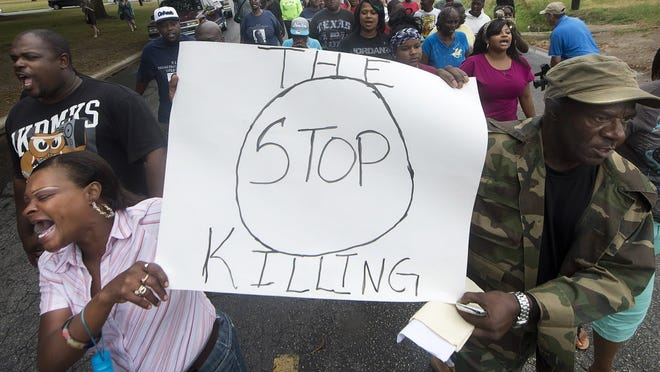K.K. Davis, left, and Tommy Jones of Hearne, Texas, carry a sign with other protesters outside the Hearne Police Department May 8, following the May 6 shooting of 93-year-old Pearlie Golden by Officer Stephen Stem.